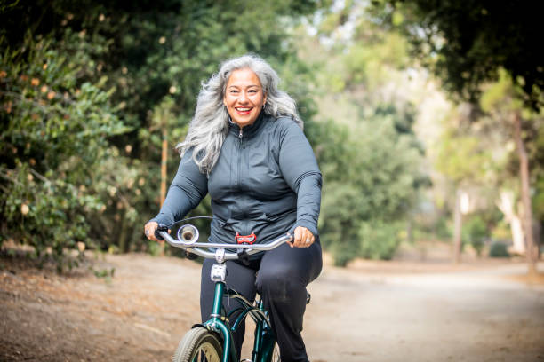 senior mexican woman riding bicycle - ciclismo foto e immagini stock