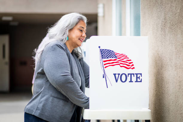 Senior Mexican Woman Voting A beautiful senior mexican woman at the voting booth women's suffrage stock pictures, royalty-free photos & images
