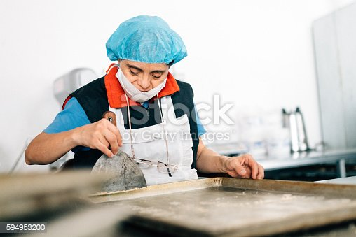 594475880istockphoto Senior Mexican woman with down syndrome working at Bakery 594953200