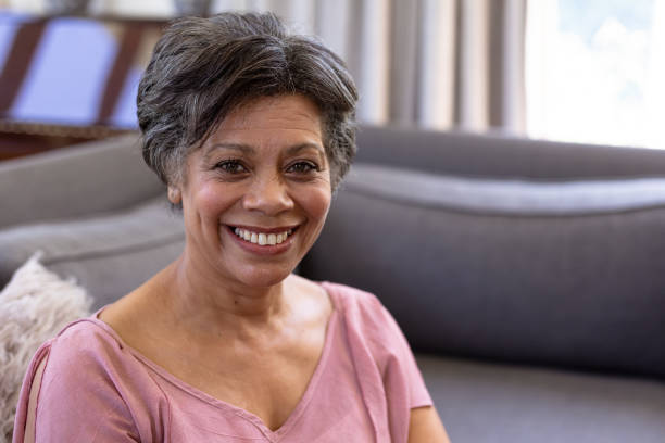 Senior mixed race woman sitting on a couch stock photo