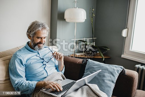 1127582480istockphoto Senior modern man with laptop at home 1196061576