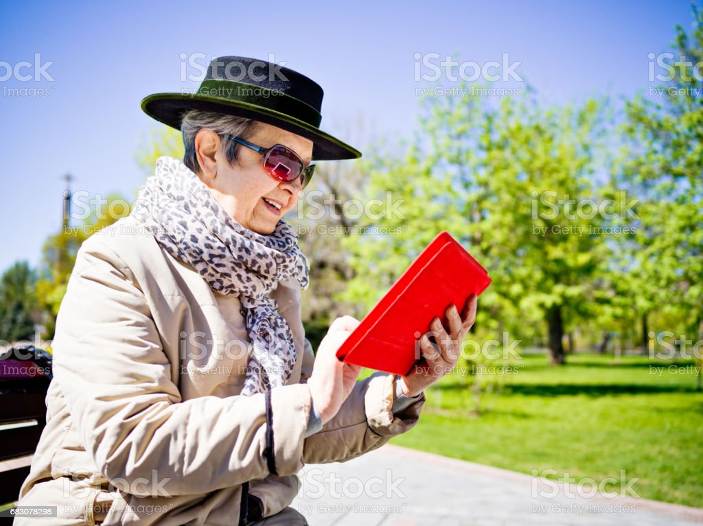 Senior modern woman with tablet in park foto de stock royalty-free