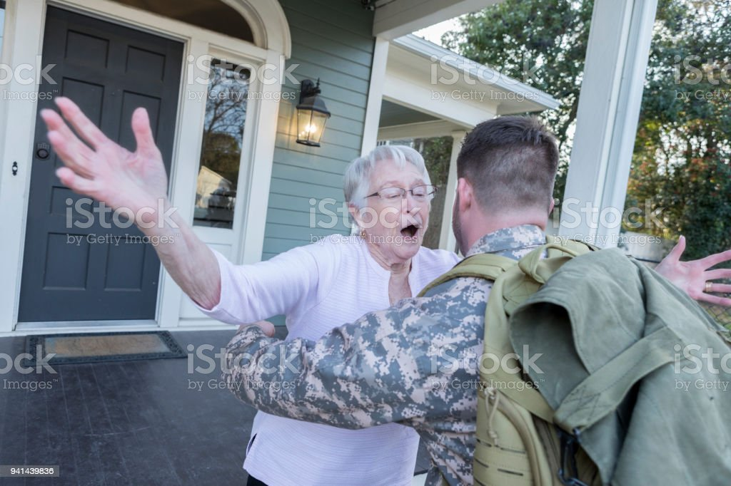 Senior mom runs to greet military son stock photo