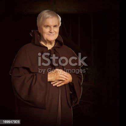 senior monk portrait - on very dark background, square composition