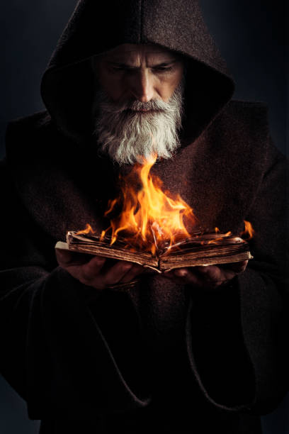 Senior monk wearing traditional clothes book in fire stock photo