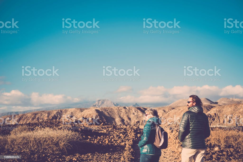Senior mother and 45 year old son spend time together walking on an isolated path. trekking and adventure journey vacation concept for people that love outdoor lifestyle. leisure activity at mountains stock photo