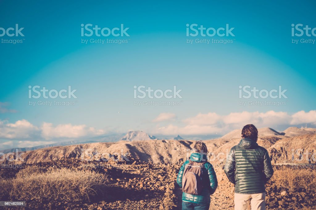 Senior mother and 45 year old son spend time together walking on an isolated path doing some trekking activity on mountains during the summer in a sunny day. vintage filter colors. looking the panorama stock photo