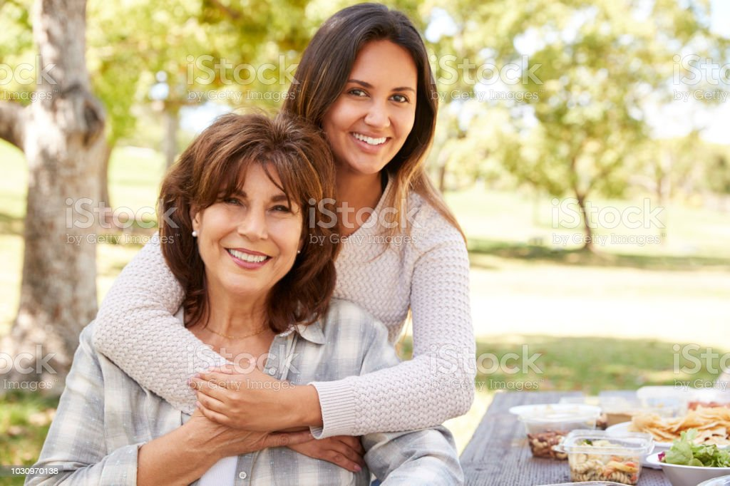 Senior mother and adult daughter embracing in park, close up stock photo