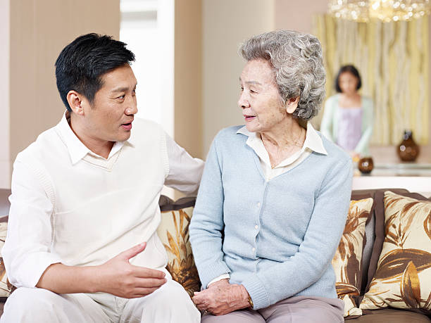 senior mother and adult son asian mother and adult son chatting on couch. old mother son asian stock pictures, royalty-free photos & images