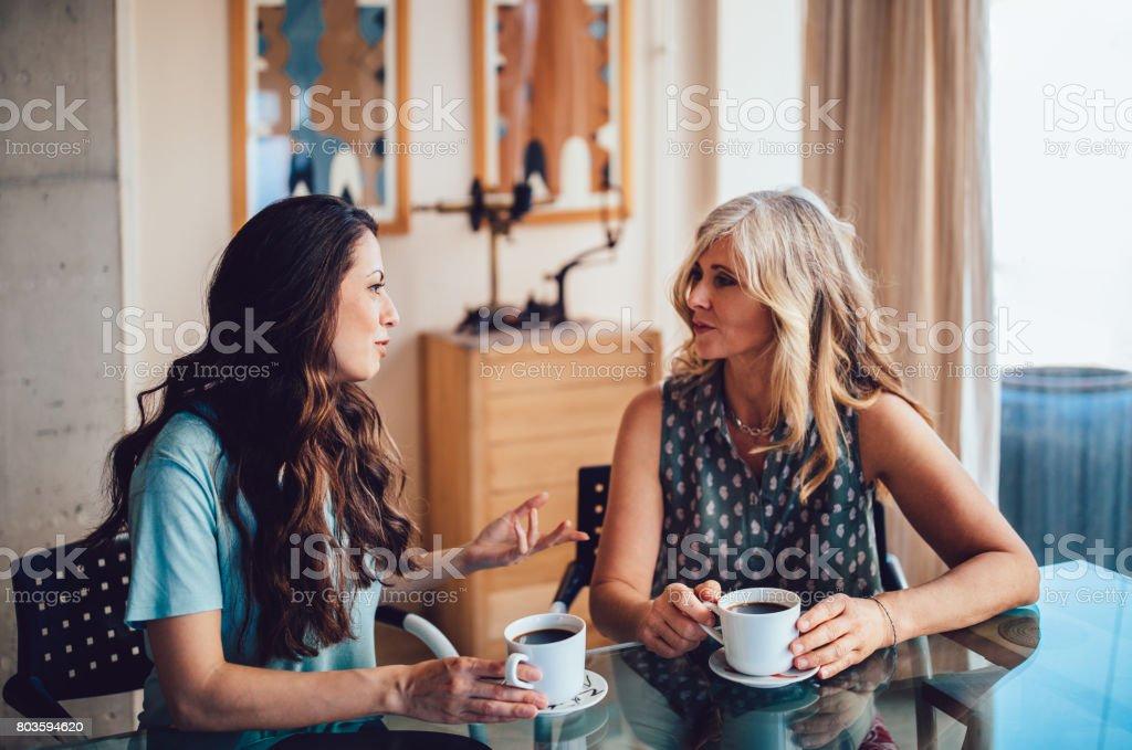 Sênior-mãe e filha tomando café juntos em casa - foto de acervo