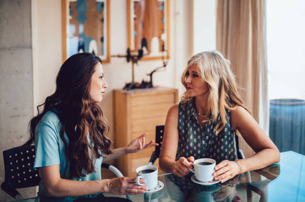 Senior mother and daughter drinking coffee together at home stock photo