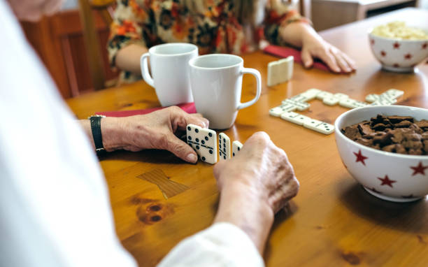 Senior mother and daughter playing domino Senior mother and daughter playing domino in the living room recreational pursuit stock pictures, royalty-free photos & images