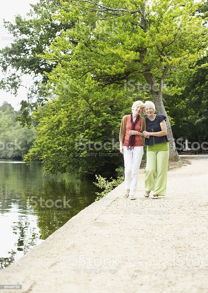 Senior mother and daughter walking near pond royalty-free stock photo