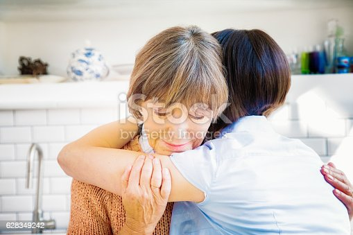 istock Senior mother hugs daughter while grieving 628349242