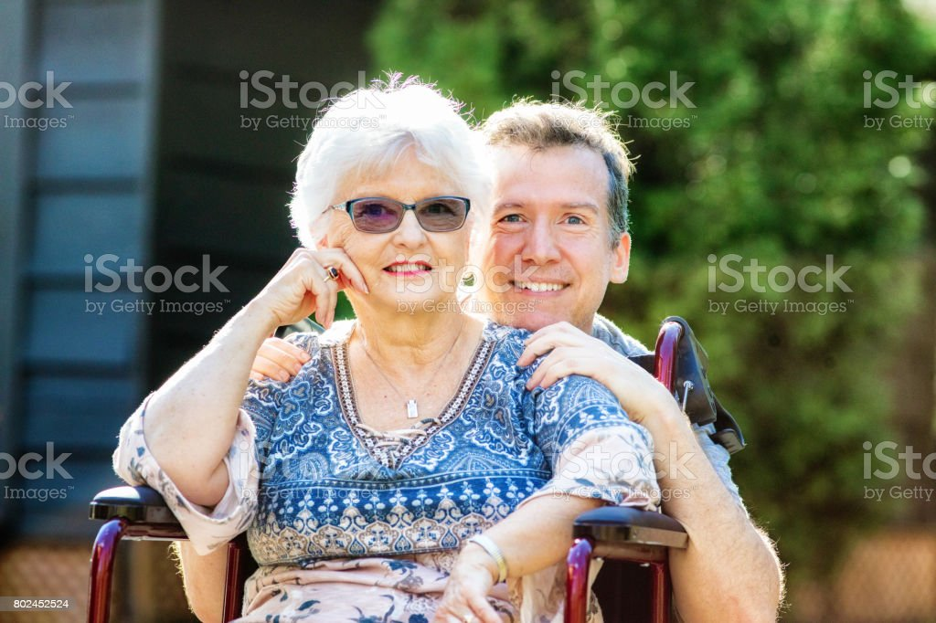 Senior mother outdoors portrait with mature son holding her shoulders stock photo
