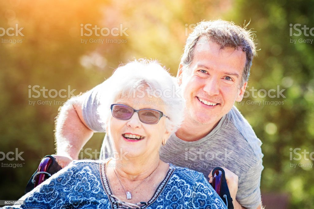 Senior mother outdoors portrait with mature son pushing her wheelchair stock photo