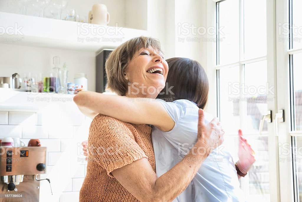 Senior mother receives a happy hug from her daughter stock photo