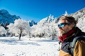 Senior man in the mountains in Winter. Lago di Fusine, Italy, Alps, Europe. All logos removed. Nikon.