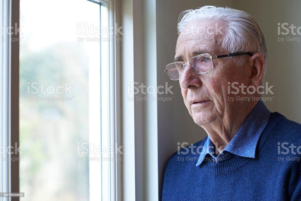 Senior MSenior Woman Suffering From Depression Looking Out Of Windowan Suffering From Depression Looking Out Of Window stock photo
