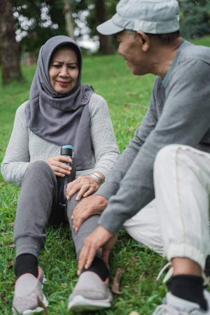 senioren-muslimische frau, die eine massage auf ihrem bein durch ehemann - granny legs stock-fotos und bilder