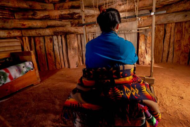 senior native american navajo frau in einem traditionellen hogan in monument valley arizona mit einem loom, um eine traditionelle indische decke zu schaffen - navajo stil stock-fotos und bilder