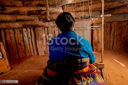 Senior Native American Navajo Woman Sitting in a Traditional Authentic Hogan Using a Homemade Loom to Create a Handwoven Blanket