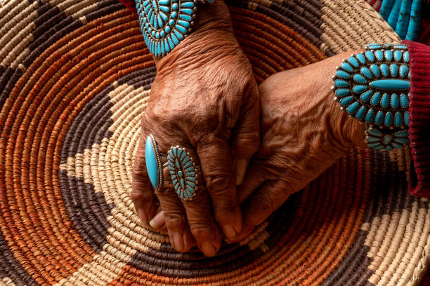 Senior Native American Navajo Woman Wearing Traditional Turquiose Jewelry Senior Navajo woman posing with traditional turquoise jewelry inside an authentic hogan indigenous peoples of the americas stock pictures, royalty-free photos & images