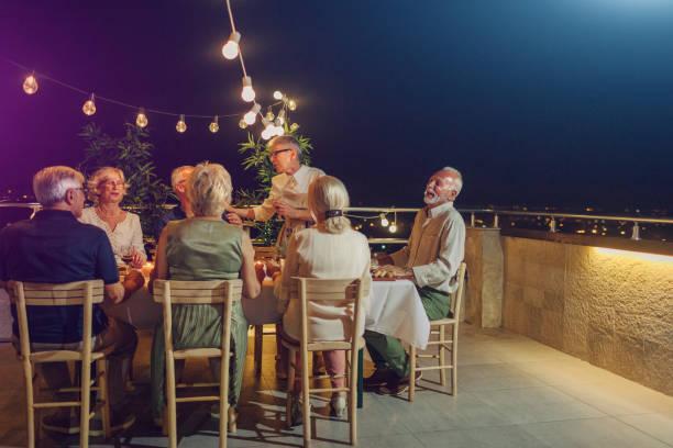 senior silvesterparty auf dem dach - terrassen lichterketten stock-fotos und bilder
