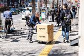 高齢者配達員がドリーを押し、新宿の路上歩道にアマゾンの箱の荷物を配達