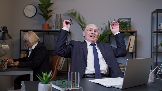 Senior old man accountant reading documents, analyzing financial papers raising hands in surprise
