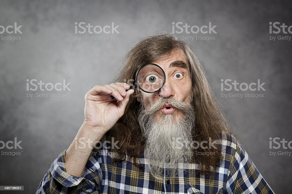 Senior old man looking through zoom magnifying glass, vision loss stock photo
