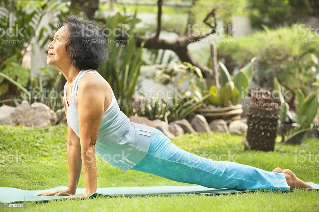 Senior old woman doing yoga in park royalty-free stock photo