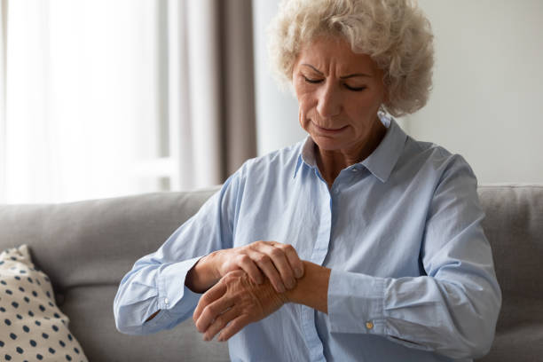Senior old woman touching wrist joint, suffering from injured hand. stock photo
