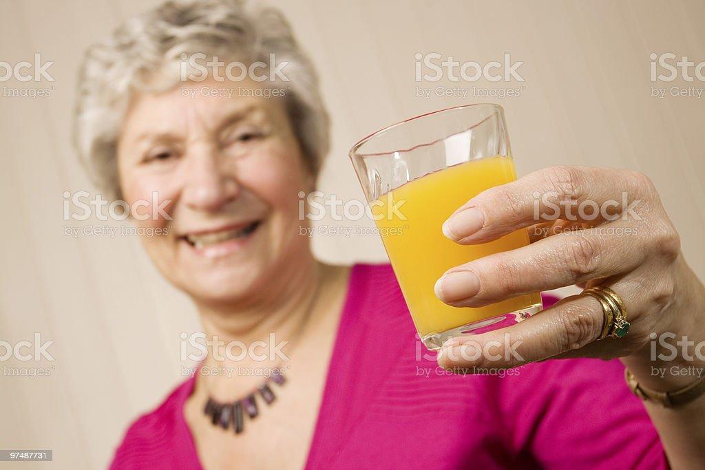 Senior older lady with glass of orange juice royalty-free stock photo