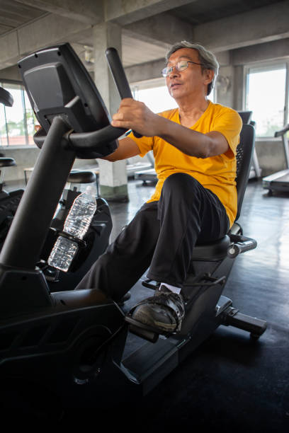 Senior older man exercising on cycling machine relaxing in fitness gym. aged . Old male workout .Mature sport training.rehabilitation.elderly Healthy lifestyle stock photo