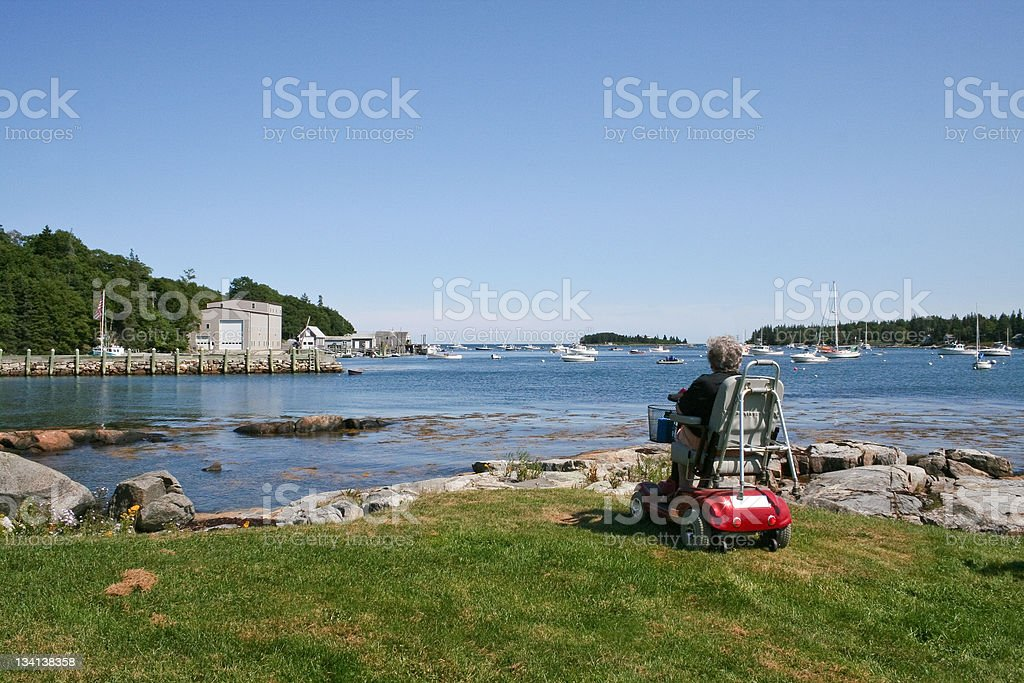 Senior on scooter overlooks harbor stock photo