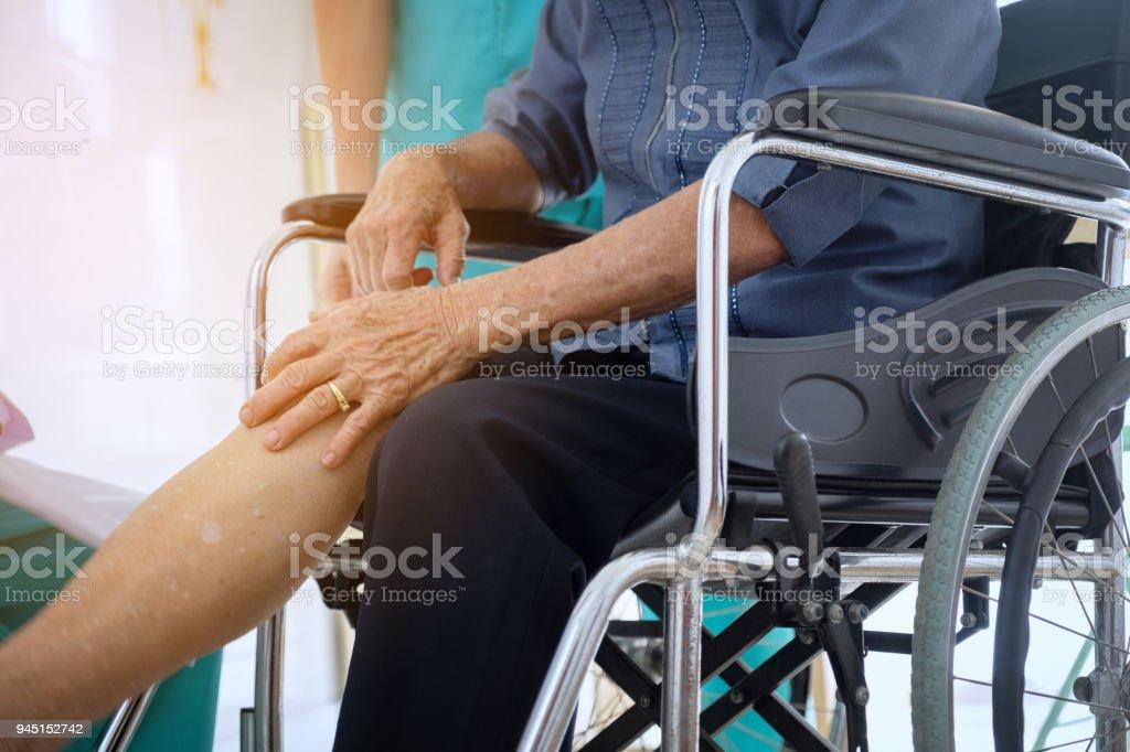 Senior oder ältere Dame Frau Patientin zeigen ihre Narben op Knie Symptome, die gemeinsame sitzen im Rollstuhl Pflege Krankenhaus leidet unter Schmerzen im Knie. – Foto