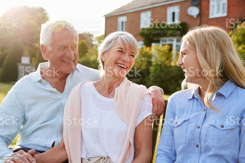 Senior Parents Sitting On Seat In Garden With Adult Daughter стоковое фото
