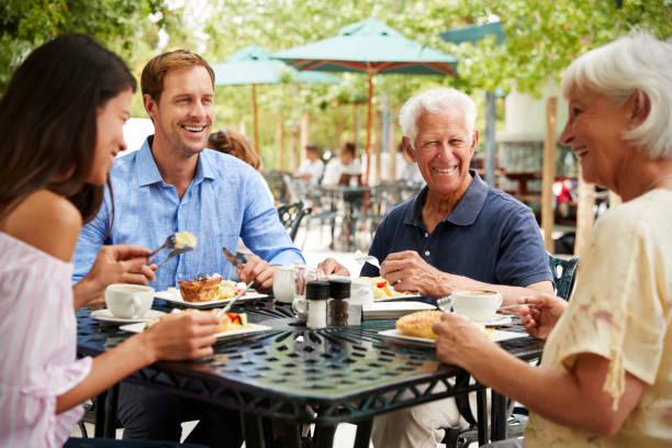 padres mayores con hijos adultos, disfrutando de comida en la cafetería al aire libre - couple lunch outdoors fotografías e imágenes de stock