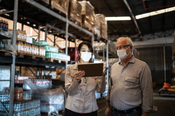 senior partners walking and using digital tablet at warehouse - with face mask - prodotti supermercato foto e immagini stock