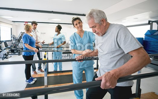 istock Senior patient and beautiful occupational theraíst walking between parallel bars 912334082