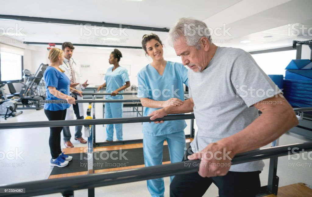 Senior patient and beautiful occupational theraíst walking between parallel bars stock photo