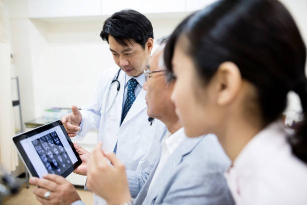 Senior patient and doctor using digital tablet in hospital ストックフォト