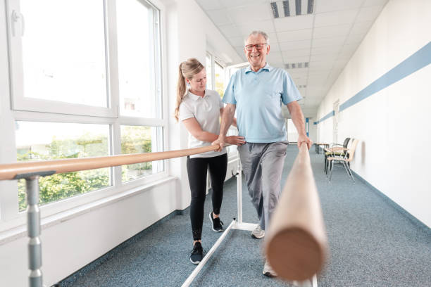 Senior Patient and physical therapist in rehabilitation walking exercises stock photo