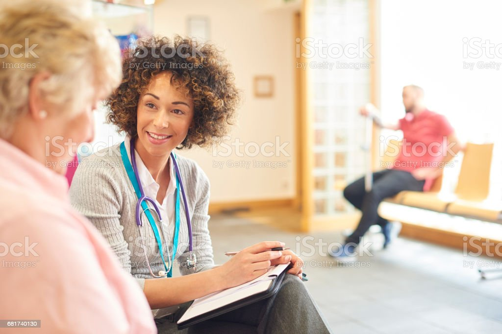 Senior patient chatting to female doctor stock photo