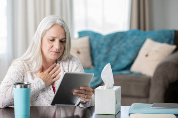 senior patient discusses pain with her doctor during video appointment - telemedicine stock pictures, royalty-free photos & images
