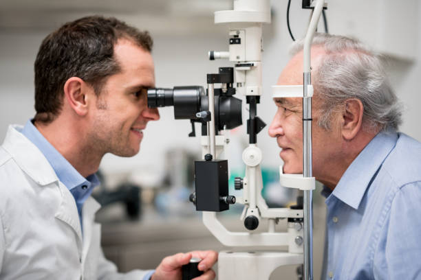 Senior patient getting an eye exam at the optician stock photo