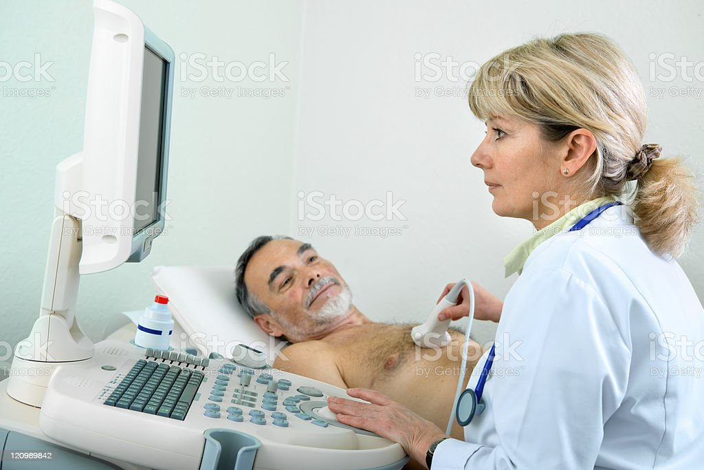 Senior patient getting ultrasound from doctor stock photo