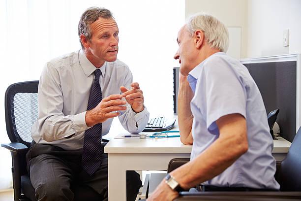 シニア患者を持つ医師との相談のオフィス - 一般開業医 ストックフォトと画像
