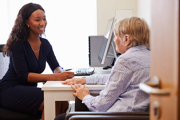 Senior Patient Having Consultation With Doctor In Office Senior Patient Having Consultation With Doctor In Office general practitioner stock pictures, royalty-free photos & images